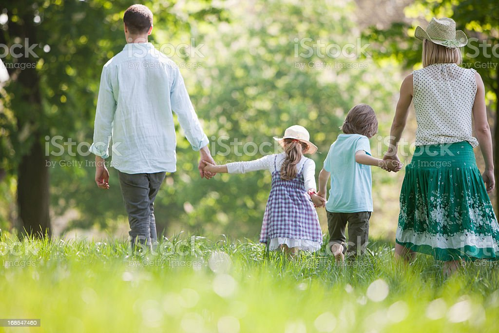 Family walking in field of flowers royalty-free stock photo