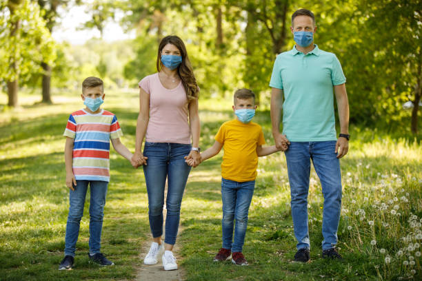 Family walking in the city park wearing anti virus masks and holding hands stock photo