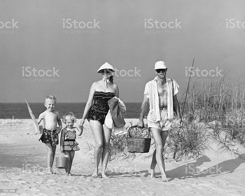 Family walking on beach, carrying fishing poles and portable cooler royalty-free stock photo