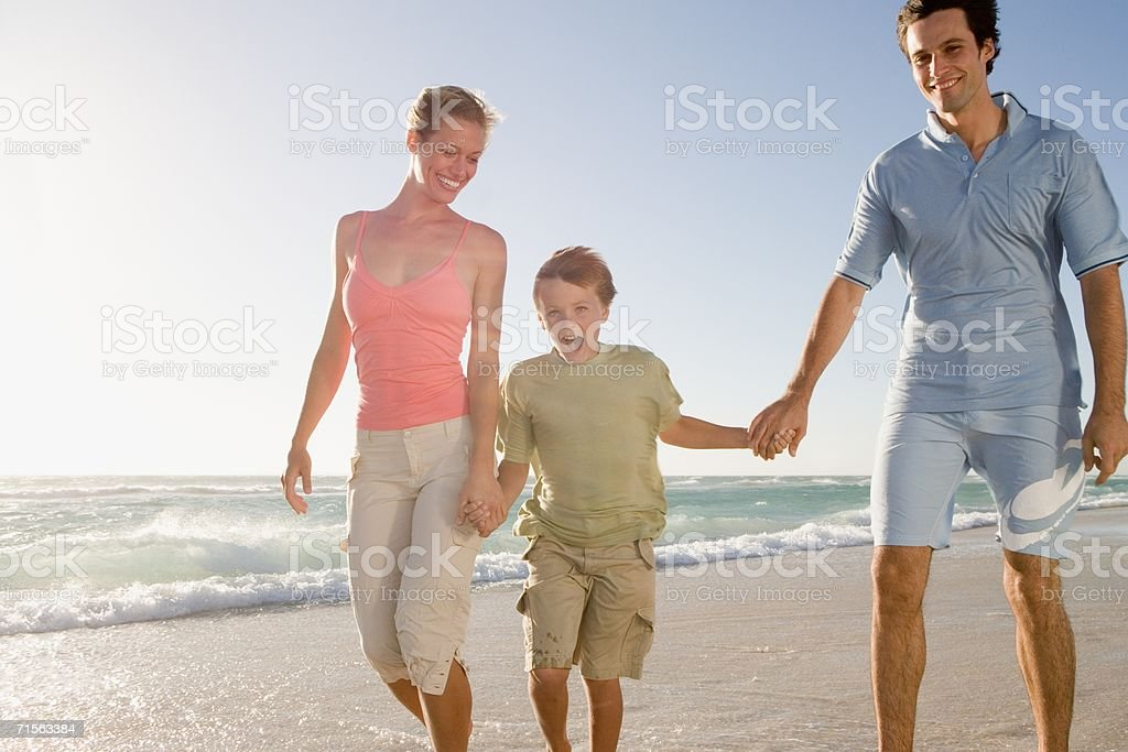 Family walking on beach in the wind stock photo