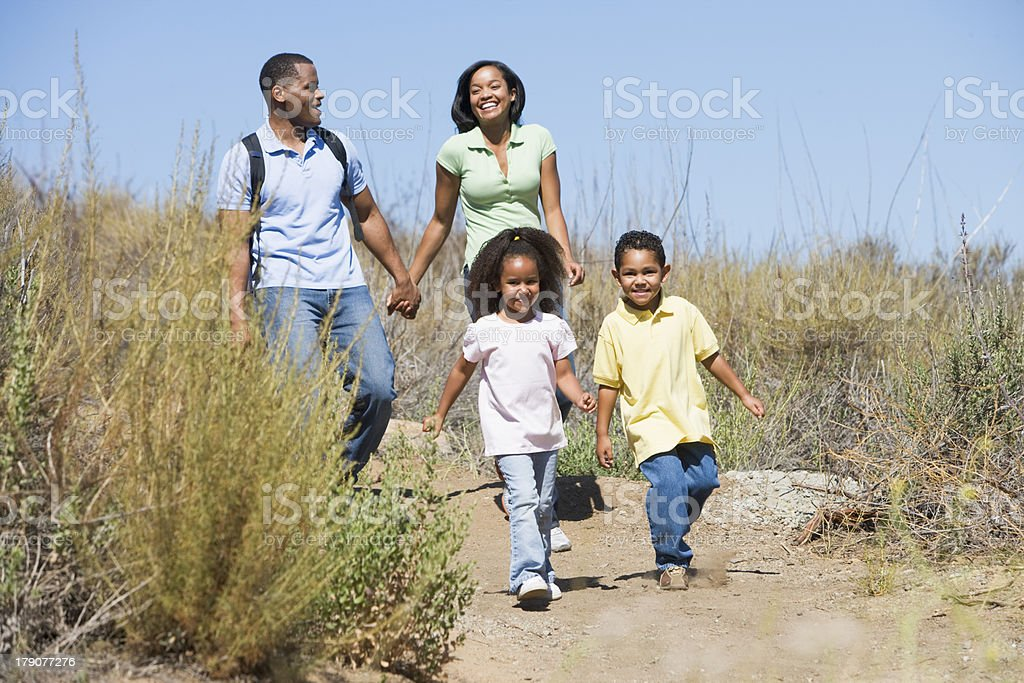 Family walking on path holding hands and smiling royalty-free stock photo