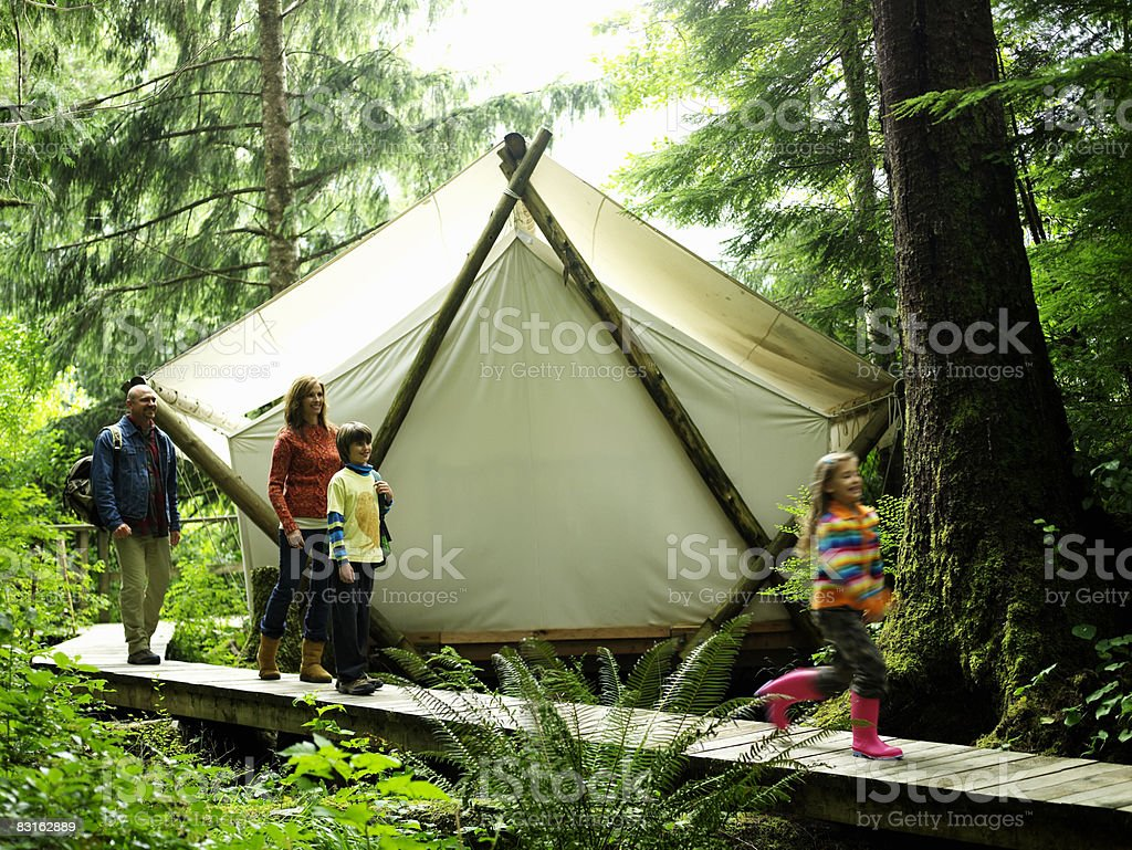 Family walking on pathway next to tent. royalty-free stock photo
