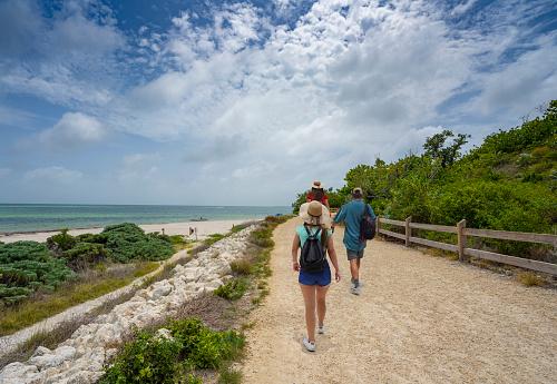 Family walking to the beach with sand dunes. People hiking on Beautiful Florida beach. Bahia Honda State Park, Florida Keys, FLorida,USA.