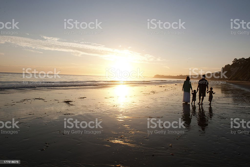 Family walking on the edge of a beach  stock photo
