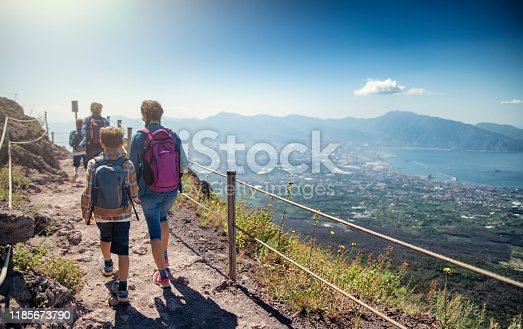 Family walking on the summit of Mount Vesuvius volcano in Campania, Italy. View of the gulf of Naples and the Lattari Mountains. Sunny summer day. Nikon D850
