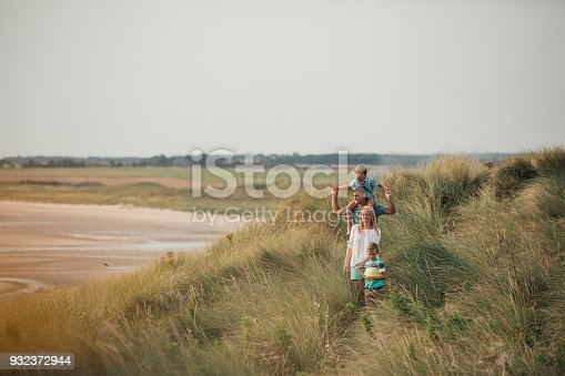 Wide angle view of a family walking through the sand dunes at the beach while on holiday.