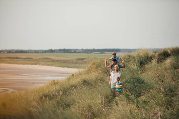 family walking through the sand dunes - uk travel stock photos and pictures