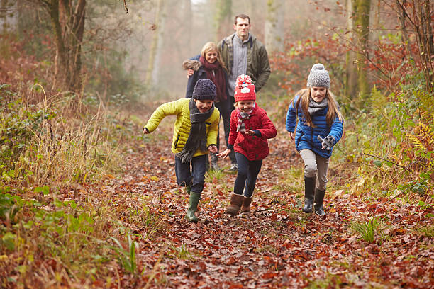 Family Walking Through Winter Woodland stock photo