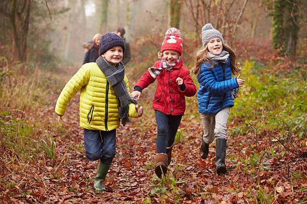 family walking through winter woodland - bos spelen stockfoto's en -beelden