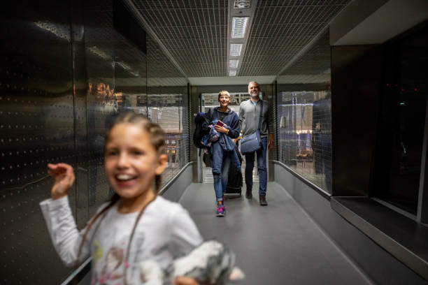 family walking thru corridor on airport departure area - focus on background stock photos and pictures
