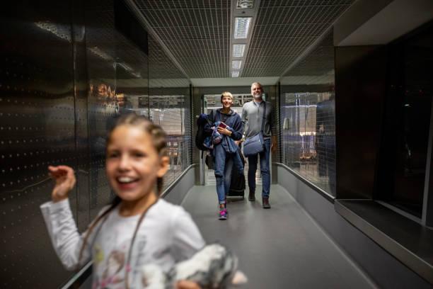 Family Walking Thru Corridor on Airport Departure Area stock photo