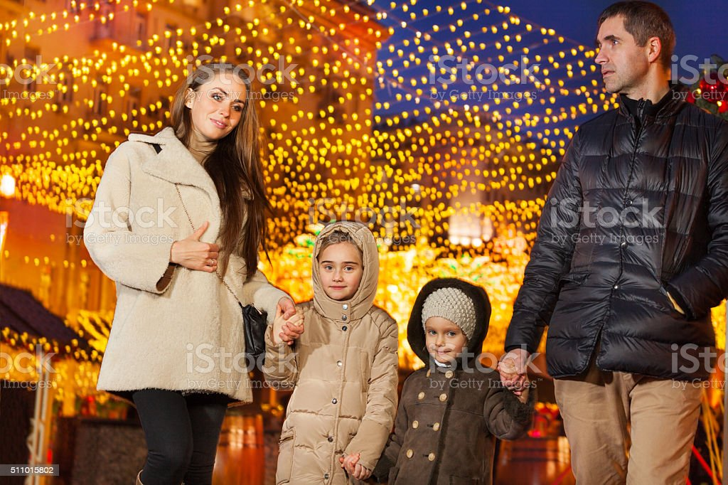 Family walking together at the holiday evening stock photo