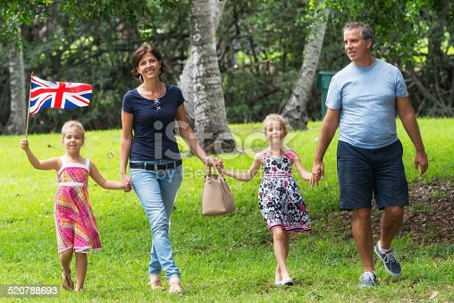 Mature couple posing with their two daughters walking at a park, one of the children is waving a british flag
