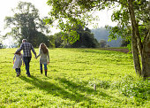 istock Family walking up a grassy hill together  84751410