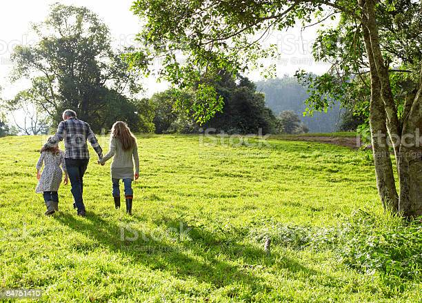 Family Walking Up A Grassy Hill Together Stock Photo - Download Image Now