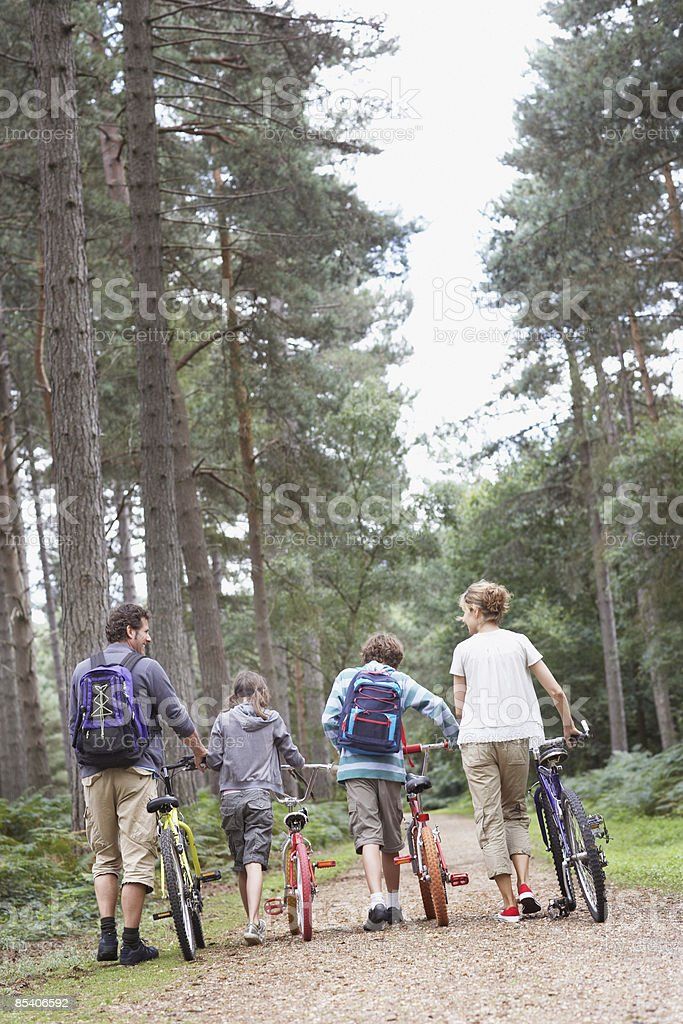 Family walking with bicycles in woods royalty-free stock photo