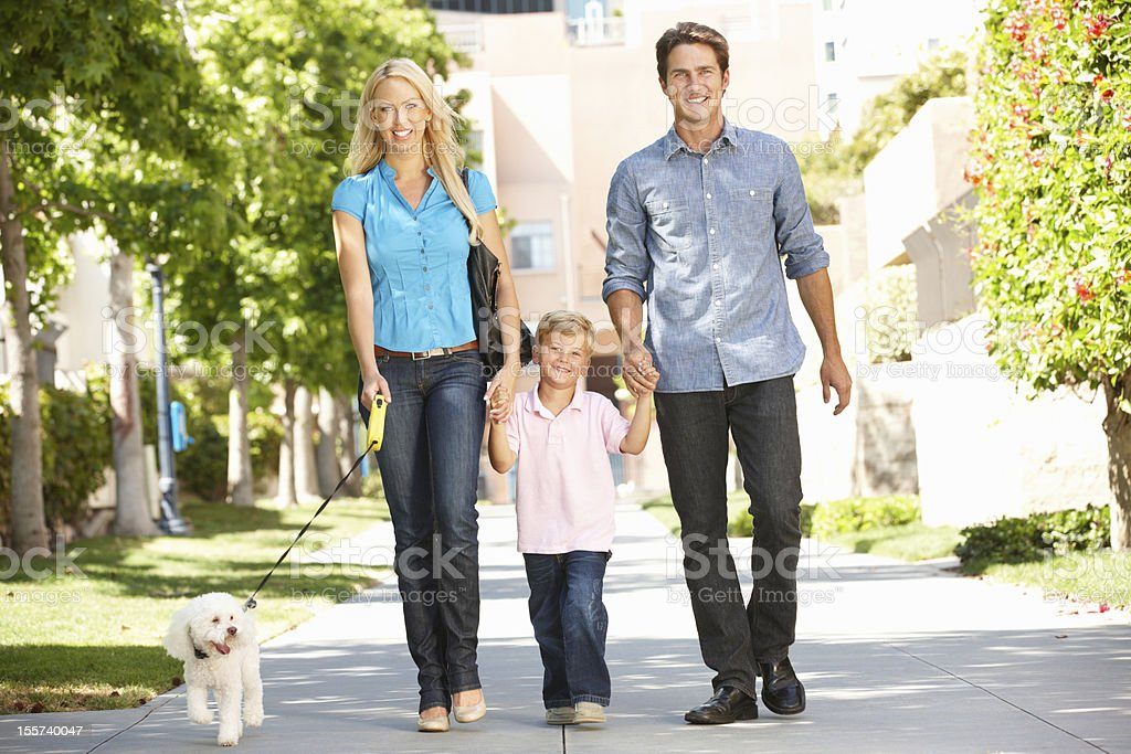 Family walking with dog in city street royalty-free stock photo