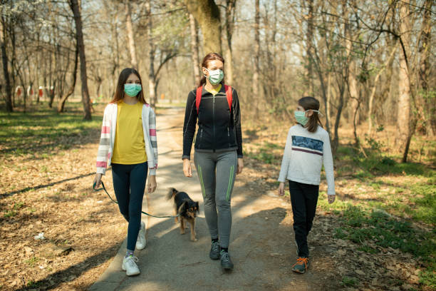 Family walking with their dog in park and wearing mask stock photo