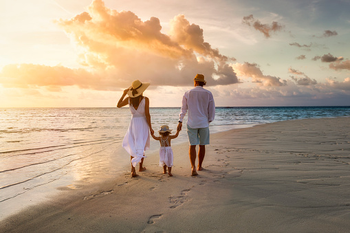 A elegant family in white summer clothing walks hand in hand down a tropical paradise beach during sunset tme and enjoys their vacation time