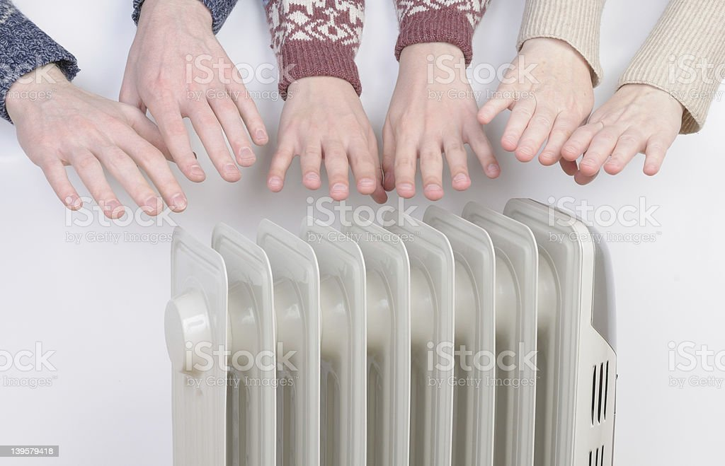 Family warming up hands over electric heater stock photo