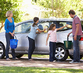 Family Washing Car Together With Buckets And Sponges.