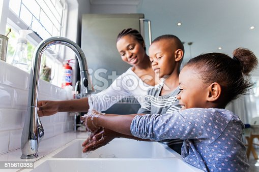 African mother opening the tap for her kids to wash their hands in the kitchen.