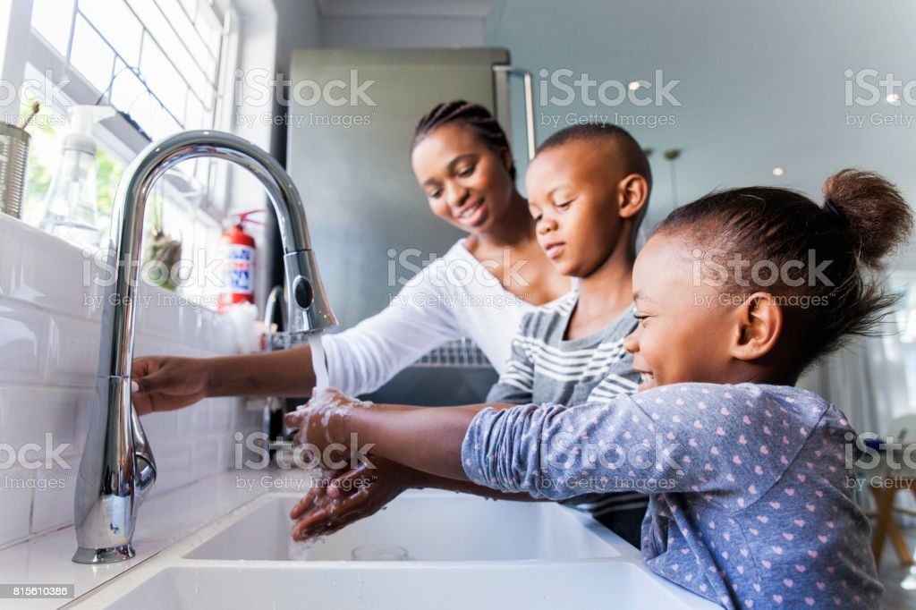 Family washing their hands together. stock photo