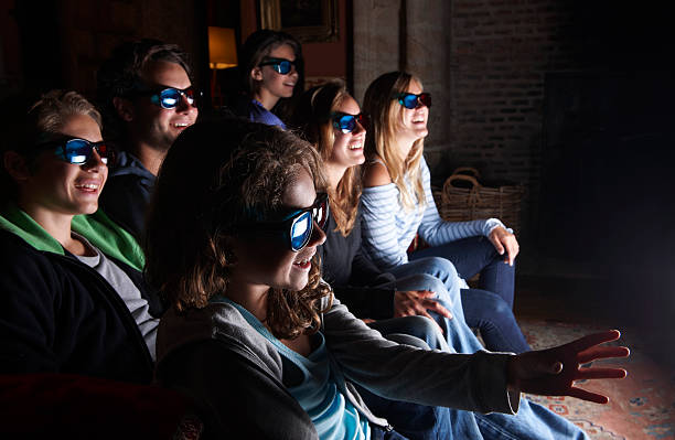 Family watching 3D television on sofa  3 d glasses stock pictures, royalty-free photos & images