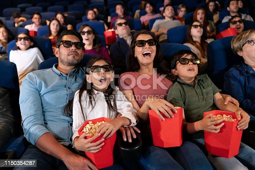 Latin American family watching a scary movie in 3D at the cinema and looking frightened - entertainment concepts