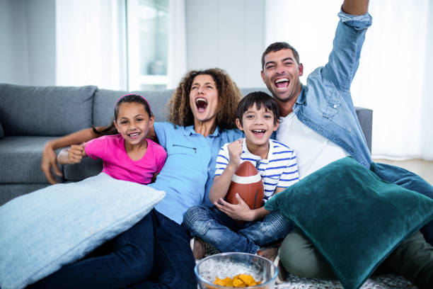Family watching american football match on television stock photo