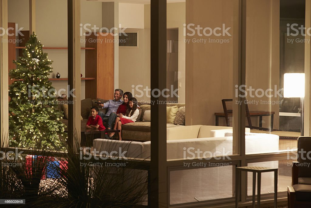 Family Watching Christmas TV At Home Viewed From Outside stock photo