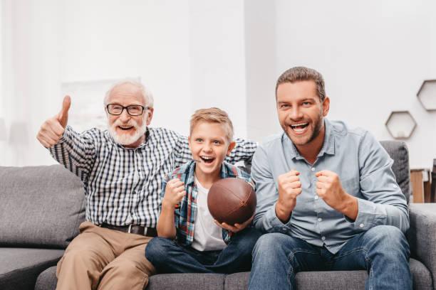 familie zu hause fußball gucken - fußball themenzimmer stock-fotos und bilder