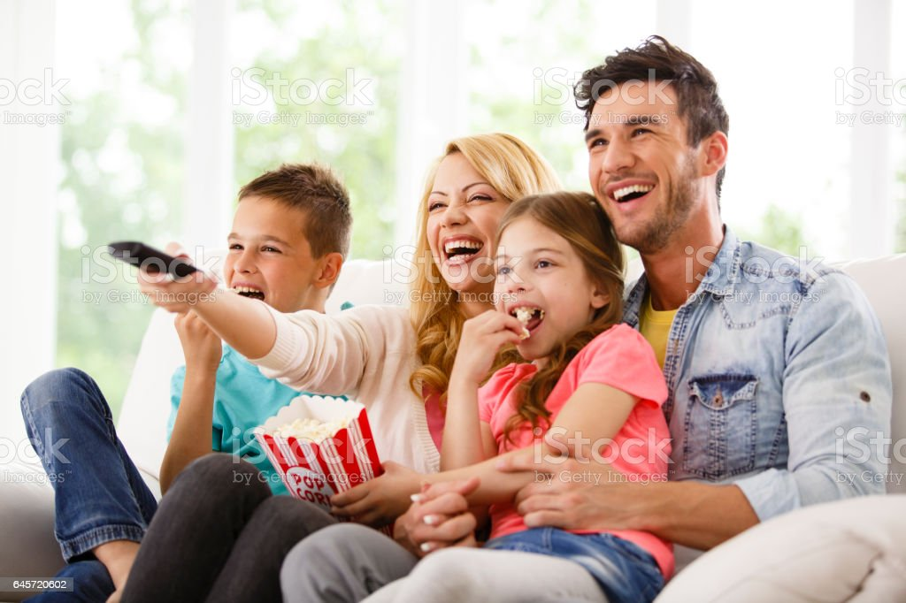 Family watching funny movie together stock photo