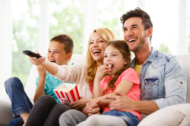 family watching funny movie together - family watching tv stock photos and pictures