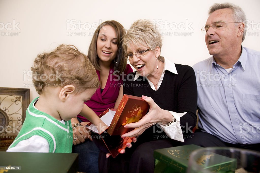 Family Watching Grandson Open Christmas Gift Box at Home royalty-free stock photo