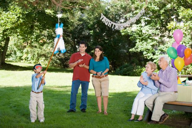 familie beobachten hispanic junge schlagen pinata auf geburtstagsparty - alles gute zum geburtstag sohn stock-fotos und bilder