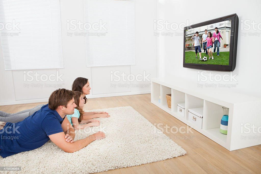 Family watching kids play football on TV stock photo