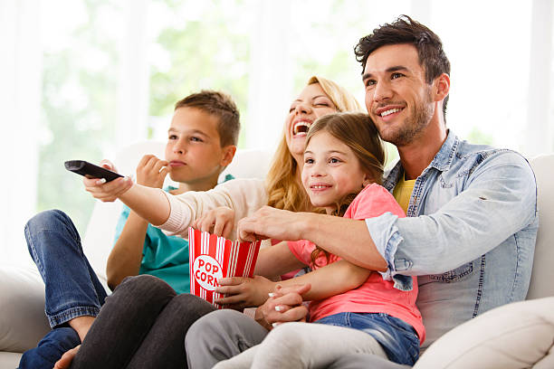 family watching television in living room - family watching tv stock photos and pictures