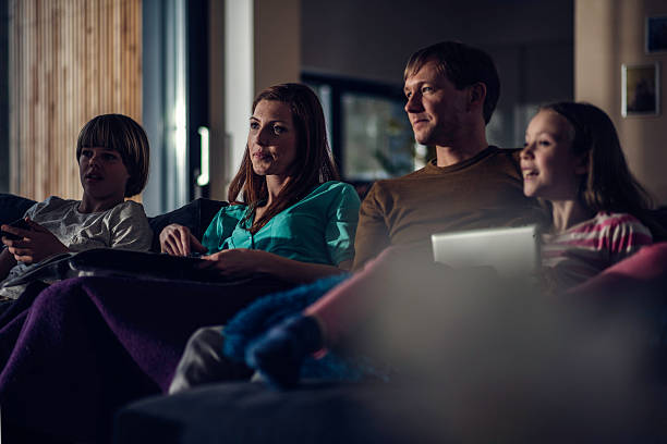 family watching television in the evening - family watching tv stock photos and pictures