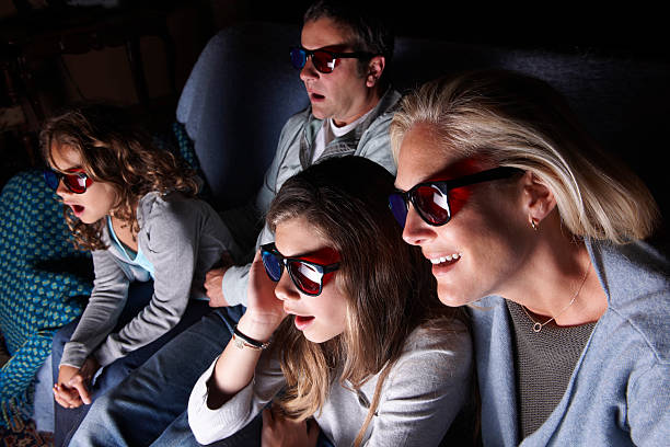 Family watching television on sofa  3 d glasses stock pictures, royalty-free photos & images