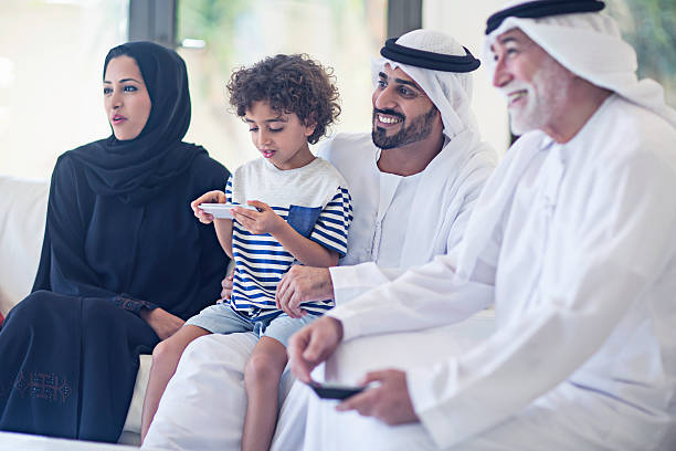 Family watching television Middle Eastern family watching television, family is enjoying watching a TV Series while the kid is playing with the mobile phone. arabic style stock pictures, royalty-free photos & images