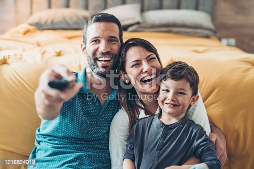 Two parents and a little boy with a TV remote control in the bedroom