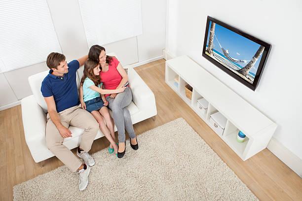 familie vor dem fernseher zu hause - küstenfamilienzimmer stock-fotos und bilder