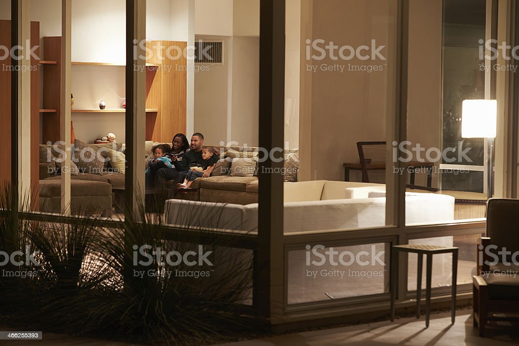 Family Watching TV At Home Viewed From Outside stock photo