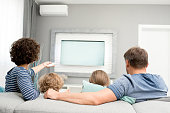 Back view portrait of happy family with two children watching TV sitting on sofa in living room and turning on modern television set with remote controller.