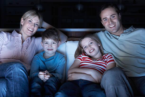familie vor dem fernseher auf sofa zusammen - serien schauen stock-fotos und bilder