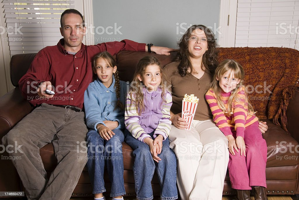 Family watching tv on the couch royalty-free stock photo