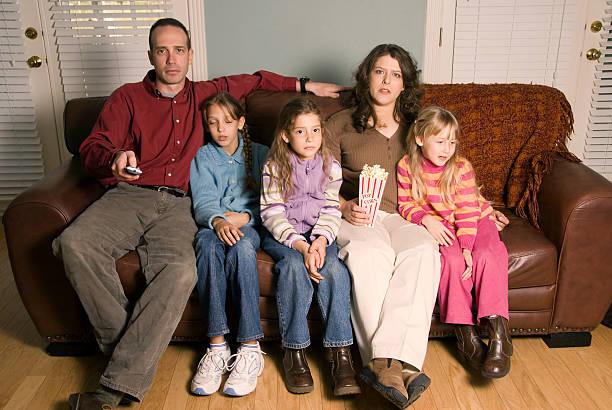 famiglia guardando la tv - divano procrastinazione foto e immagini stock