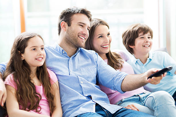 family watching tv - family watching tv stock photos and pictures