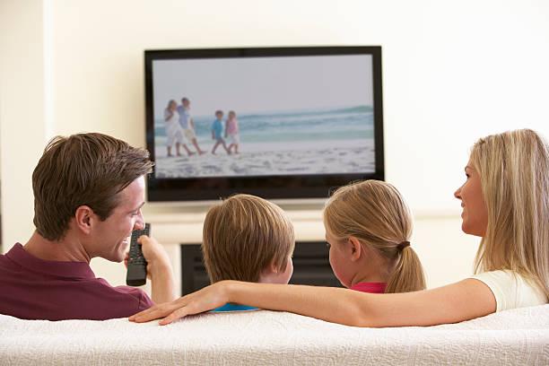 família assistir tv de ecrã panorâmico em casa - tv e familia e ecrã imagens e fotografias de stock